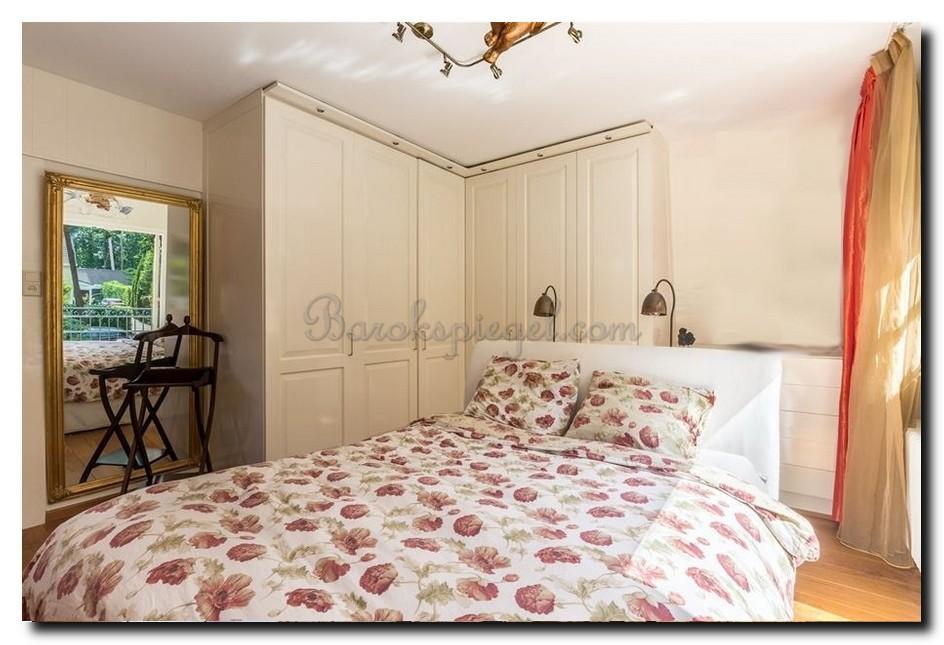 Grote spiegel gouden lijst naast het bed in slaapkamer tegenover raam raameffect